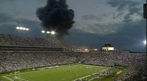Smoke rises over Jordan-Hare Stadium during the 1996 Auburn-LSU game as the old Sports Arena, used by the gymnastics team, burns. (YouTube image)